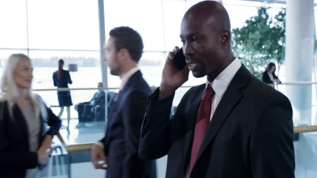 ds african-american business man walking through the business lounge at the airport and talking on the phone - males stock videos & royalty-free footage