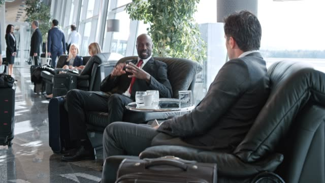 ds african-american businessman and his caucasian colleague talking in the business lounge at the airport - gate stock videos & royalty-free footage