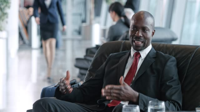 african-american businessman having a discussion with his colleague in the business lounge at the airport - gate stock videos & royalty-free footage