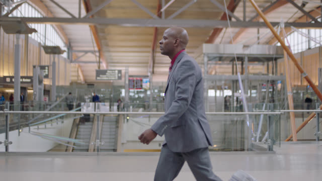 african-american businessman rolls suitcase through airport terminal near entrance. - profile stock-videos und b-roll-filmmaterial