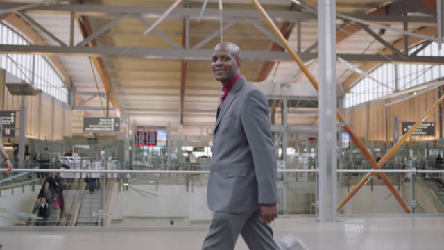 slo mo. african-american businessman rolls suitcase through airport, turns to camera, smiles. - 旅行かばん点の映像素材/bロール