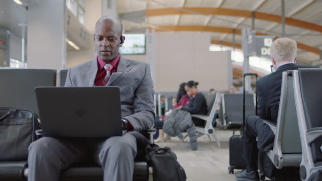 African-American businessman with laptop talks on hands-free device in waiting area near gate.