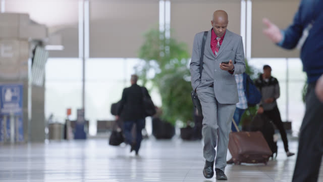 slo mo. african-american businessman with smart phones walks through bustling airport terminal. - コンコース点の映像素材/bロール