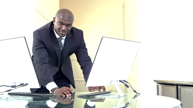 African-American businessman with two computers