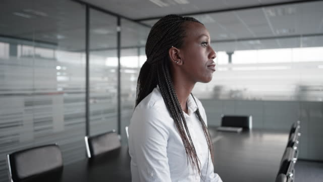 african-american businesswoman gazing out the window in an empty conference room - individuality stock videos & royalty-free footage