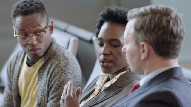 african-american businesswoman works on tablet and talks with colleagues at airport terminal gate. - viaggio di lavoro video stock e b–roll