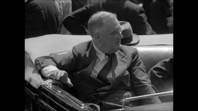 vidéos et rushes de african-american children in crowd holding u.s. flags. president franklin d. roosevelt sitting in convertible car. african-american children waving... - 1939