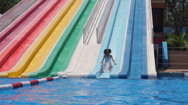 vídeos de stock e filmes b-roll de african-american children slide slow motion on slider in water park on summer holiday.water splash on pool is beauty. - escorrega de água