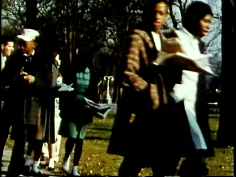 vidéos et rushes de 1963 ms african-american children walking with white adults in park / chicago, united states / audio - chicago illinois