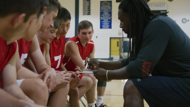 african-american coach discussing a play with his  high school basketball team - basketball sport stock videos & royalty-free footage