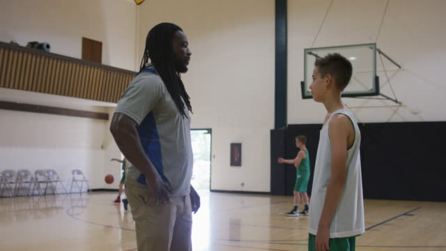 african-american coach pulling a player aside for a conversation - junior high stock videos & royalty-free footage