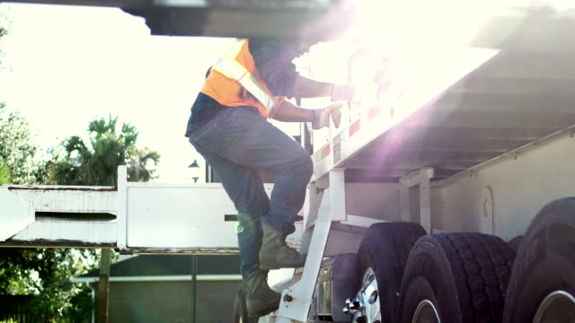 african-american construction worker climbing onto truck - moving up stock videos & royalty-free footage