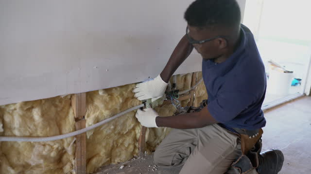 african-american construction worker installing fiberglass insulation on wall panel during wood frame house construction - insulator stock videos & royalty-free footage