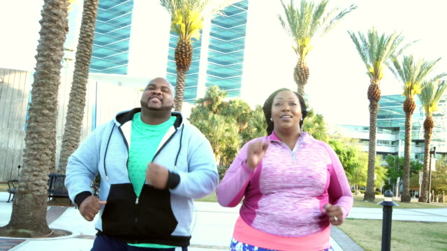 african-american couple power walking in city park - overweight active stock videos & royalty-free footage