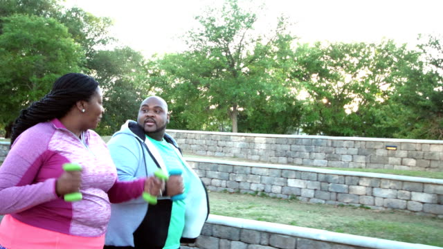 african-american couple power walking in city park - racewalking stock videos and b-roll footage