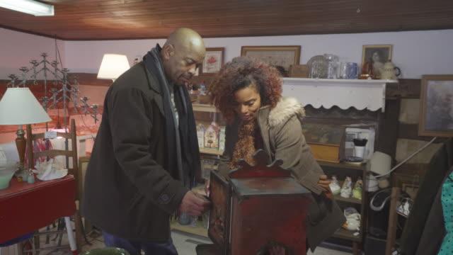 vidéos et rushes de boutique de couple afro-américain au magasin d'antiquités - brocante