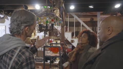 vidéos et rushes de boutique de couple afro-américain au magasin d'antiquités - antiquités