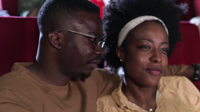 african-american couple watching a romantic movie and having fun at the cinema - film industry stock videos & royalty-free footage