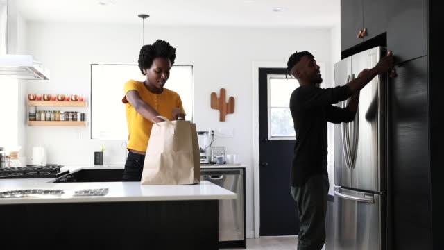 vidéos et rushes de couple afro-américain travaillant dans la cuisine à domicile prépare le déjeuner - sac de shopping