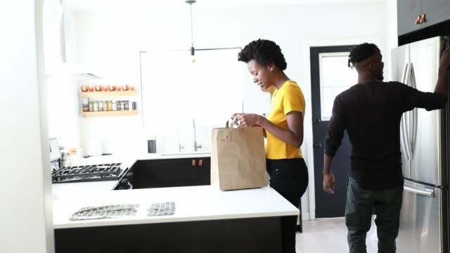 vidéos et rushes de couples afro-américains travaillant dans la cuisine à la maison préparant le déjeuner - sac de shopping