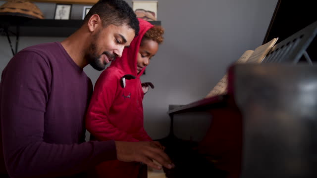 vídeos de stock e filmes b-roll de african-american dad learning his daughter how to play piano - piano
