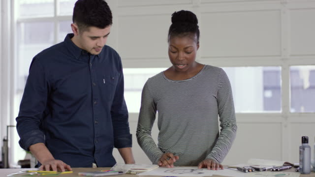 African-American Designer Reviewing a Sketch with Her Filipino Colleague