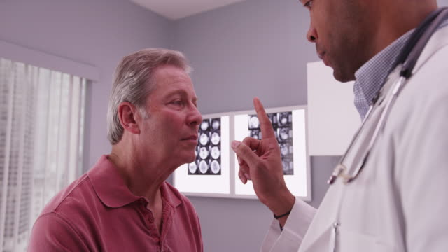 vídeos de stock, filmes e b-roll de african-american doctor examining head trauma of senior caucasian patient - physical injury