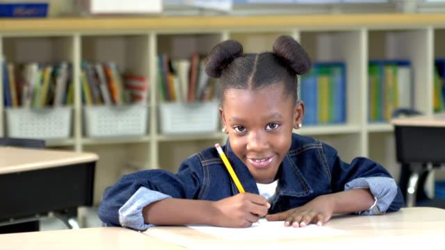 afro-amerikanska elementary student skriver i klassen - 6 7 år bildbanksvideor och videomaterial från bakom kulisserna