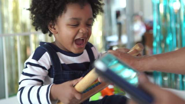 vídeos de stock, filmes e b-roll de afro-americano etnia menino menino aprendendo fazendo em casa com os pais , conceito de educação domiciliar , scramble para brinquedos e menino egoísmo - pegar
