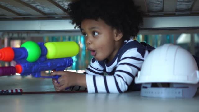 vídeos de stock, filmes e b-roll de menino da etnia afro-americana jogando pistola de esguicho e segurando bandeira americana - escondendo