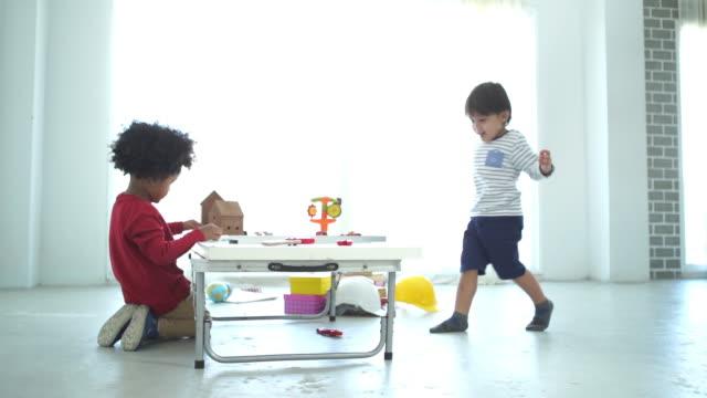 vídeos de stock, filmes e b-roll de menino da etnia afro-americana jogando bloco de brinquedos com seu amigo - unidade