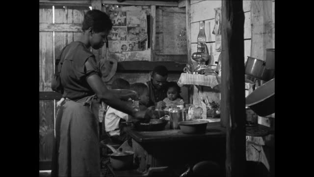 africanamerican family hut shanty ws negroamerican women washing clothes in bin village bg int ms family woman cooking on stove cu father feeding... - scrubs stock videos & royalty-free footage