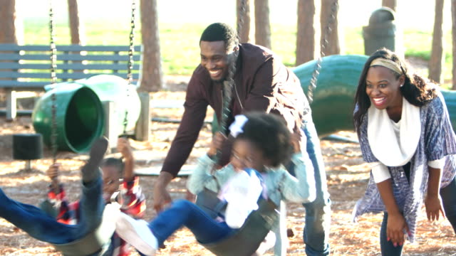 african-american family playing on playground swing - parco giochi video stock e b–roll