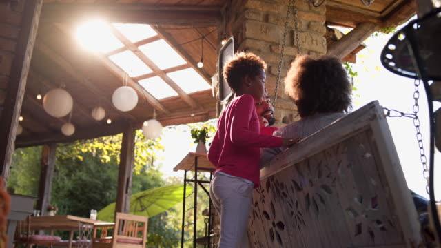 vídeos de stock e filmes b-roll de african-american family swinging on porch swing - alpendre