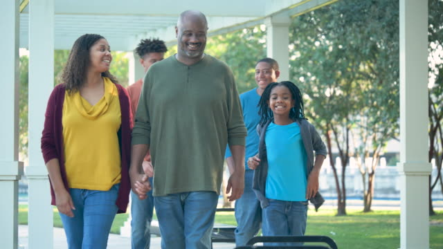 african-american family walking outdoors, sit on bench - family with three children stock videos & royalty-free footage