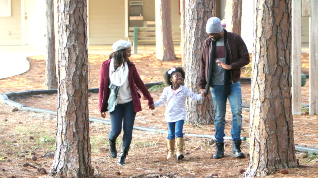 african-american family with girl walking thru trees - minoranza video stock e b–roll