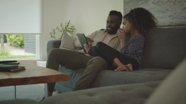 African-American Father and daughter looking at tablet in living room at home