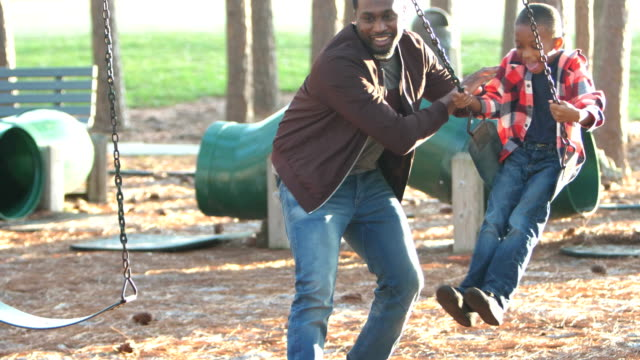african-american father and son on playground swing - swinging stock videos & royalty-free footage
