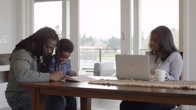 African-American Father Colors with His Son While His Wife Works on a Laptop