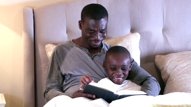 african-american father reading bedtime story to son - electric lamp stock videos & royalty-free footage