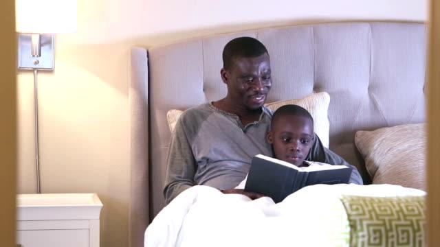 vídeos y material grabado en eventos de stock de padre afroamericano leyendo la historia de la hora de dormir a hijo - 30 39 years