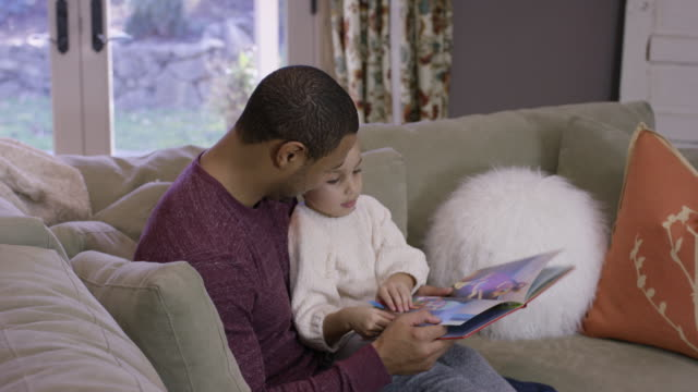African-American Father Reading to His Daughter on the Couch