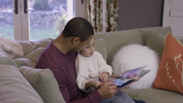 Lecture de père afro-américain à sa fille sur le canapé