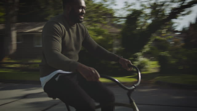 African-American father rides bike in neighborhood with daughters