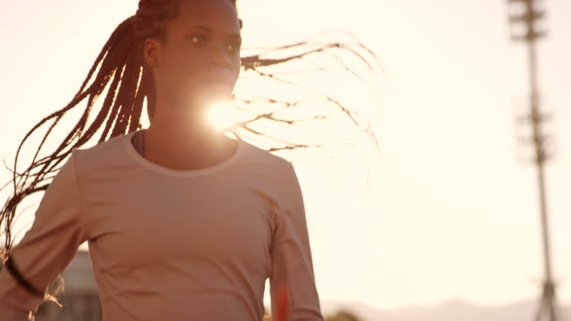 slo mo ds african-american female athlete running in the sunny stadium at sunset - forza video stock e b–roll