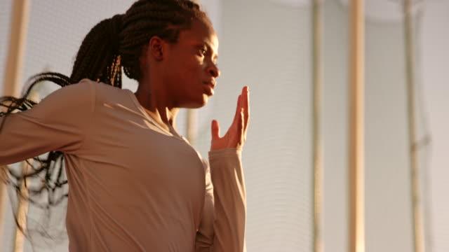 夕暮れ時スタジアムで実行して編んだ髪と slo mo ts アフリカ系アメリカ人の女性アスリート - strength点の映像素材/bロール