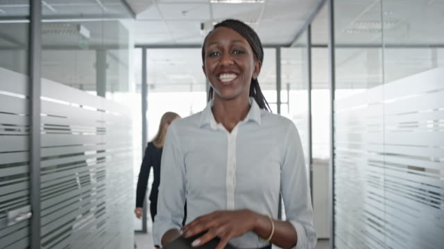 African-American female office employee smiling as she walks down the office hallway