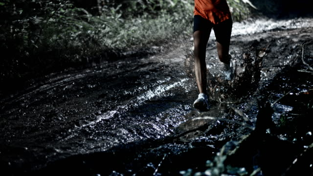SLO MO African-American female running on a muddy trail at night