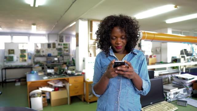afrikanisch-amerikanische arbeitnehmerin mit handy im ingenieurbüro - industrieberuf stock-videos und b-roll-filmmaterial