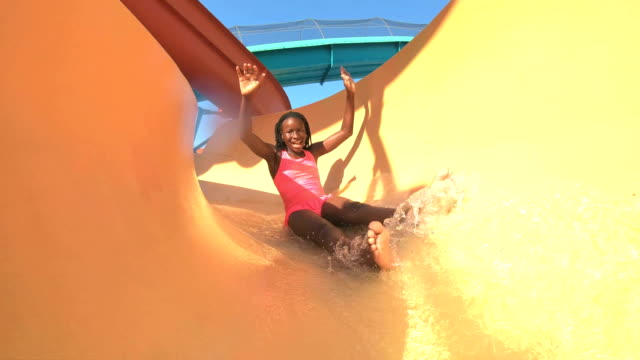 african-american girl sliding down water slide - sliding stock videos & royalty-free footage